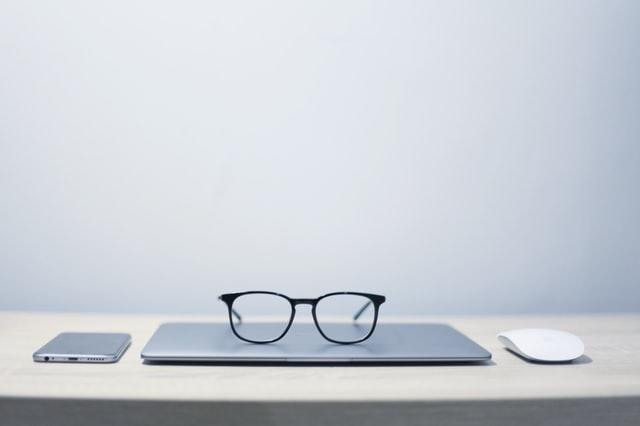 Melnās brilles uz pelēkā datora. Digitālā Mārketinga Aģentūra Omarketing